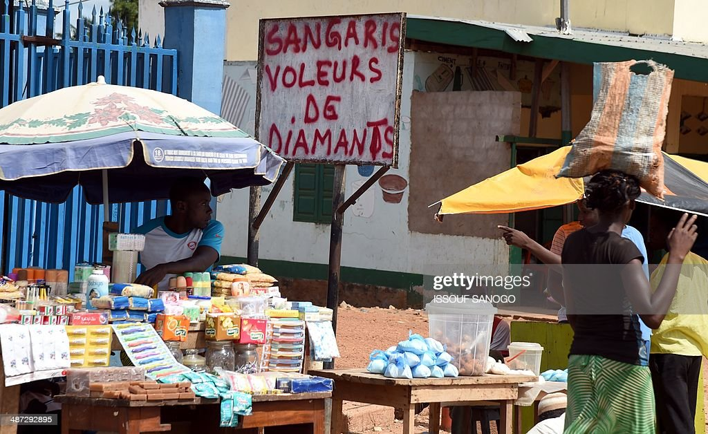 A Central African vendor sells products near a sign covered with a graffiti inscription reading 'Sangaris - diamond thieves', in the PK5 neighborhood of Bangui, on April 29, 2014. Two civilians were killed when gunmen ambushed a convoy of Muslims fleeing violence in the capital of the strife-torn Central African Republic, international peacekeepers said today.