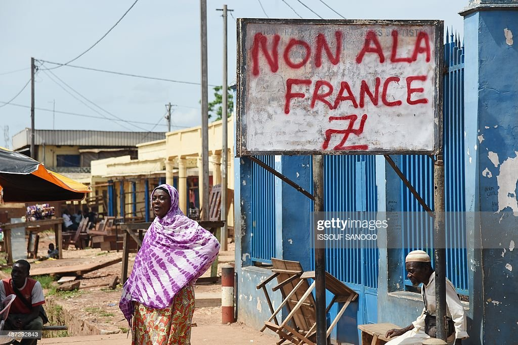 Central Africans stand near a sign with a graffiti inscription reading 'No to France' and a Swastika symbol, in the PK5 neighborhood of Bangui, on April 29, 2014. Two civilians were killed when gunmen ambushed a convoy of Muslims fleeing violence in the capital of the strife-torn Central African Republic, international peacekeepers said today. AFP PHOTO / ISSOUF SANOGO