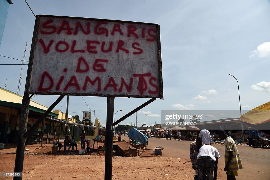 Central Africans walk near a sign covered with a graffiti inscription reading 'Sangaris - diamond thieves', in the PK5 neighborhood of Bangui, on April 29, 2014. Two civilians were killed when gunmen ambushed a convoy of Muslims fleeing violence in the capital of the strife-torn Central African Republic, international peacekeepers said today. AFP PHOTO / ISSOUF SANOGO