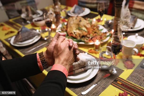 Central American immigrants and their families pray before Thanksgiving dinner on November 24 2016 in Stamford Connecticut Family and friends some of...