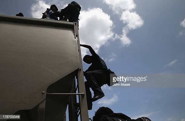 Central American immigrants arrive on top of a freight train for a stop on August 6 2013 in Ixtepec Mexico Thousands of Central American migrants...