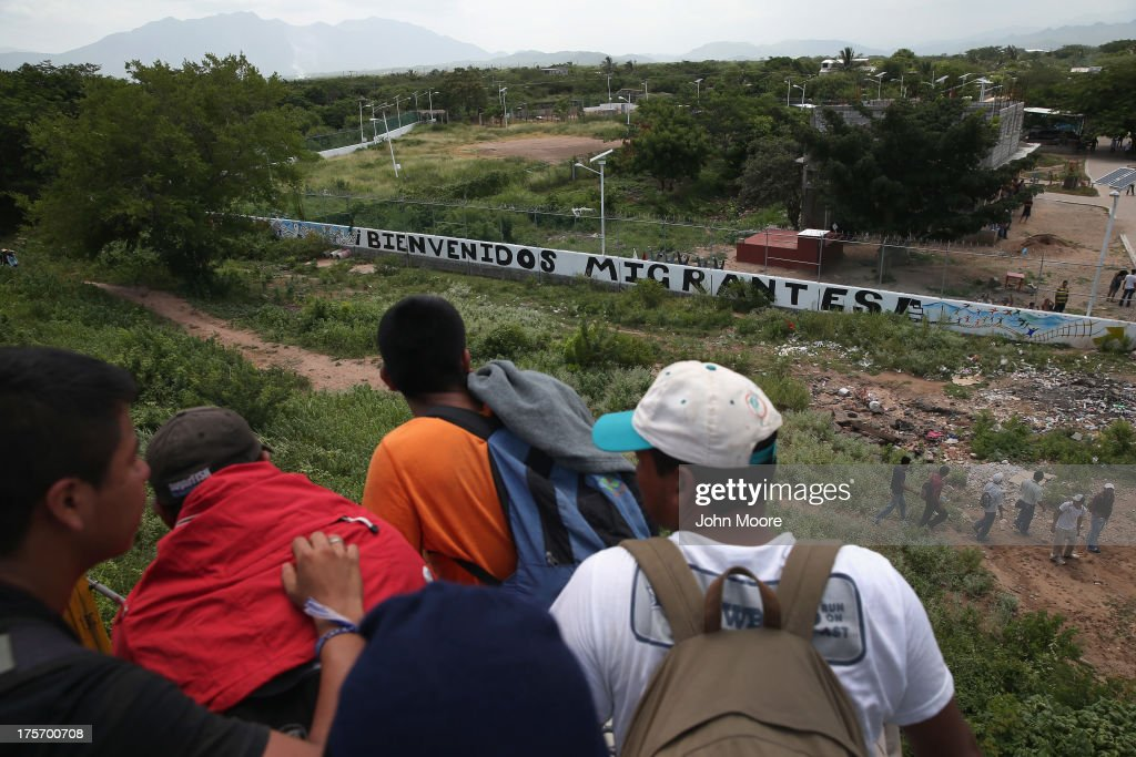 Central American immigrants arrive on top of a freight train to the Hermanos en el Camino immigrant shelter on August 6, 2013 in Ixtepec, Mexico. The sign outside reads 'Welcome Migrants.' Thousands of Central American migrants ride the trains, known as 'la bestia', or the beast, during their long and perilous journey north through Mexico to reach the United States border. Some of the immigrants are robbed and assaulted by gangs who control the train tops, while others fall asleep and tumble down, losing limbs or perishing under the wheels of the trains. Only a fraction of the immigrants who start the journey in Central America will traverse Mexico completely unscathed - and all this before illegally entering the United States and facing the considerable U.S. border security apparatus designed to track, detain and deport them.