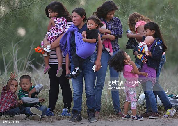Central American immigrants await transportation to a US Border Patrol processing center after crossing the Rio Grande from Mexico into the Texas on...