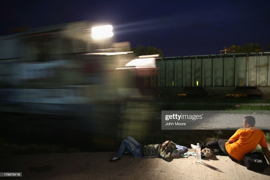 A Central American immigrants prepare to climb aboard a freight train headed north early on August 4, 2013 in Arriaga, Mexico. Thousands of migrants ride atop the trains, known as 'la bestia,' or the beast, during their long and perilous journey through Mexico to the U.S. border. Many of the immigrants are robbed or assaulted by gangs who control the train tops, while others fall asleep and tumble down, losing limbs or perishing under the wheels of the trains. Only a fraction of the immigrants who start the journey will arrive safely on their first attempt to illegally enter the United States.
