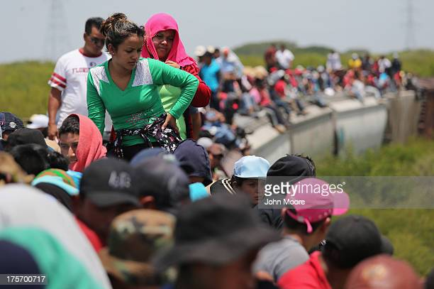 Central American immigrants ride north on top of a freight train on August 6 2013 near Juchitan Mexico Thousands of Central American migrants ride...