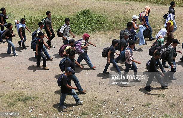 Central American immigrants walk after arriving atop a freight train for a stop on August 6 2013 to Ixtepec Mexico Thousands of Central American...