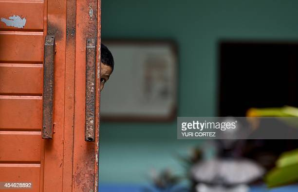 A Central American migrant child who is accompanied by his mother watches behind the main door of the Bethlehem Shelter where they arrived to make a...