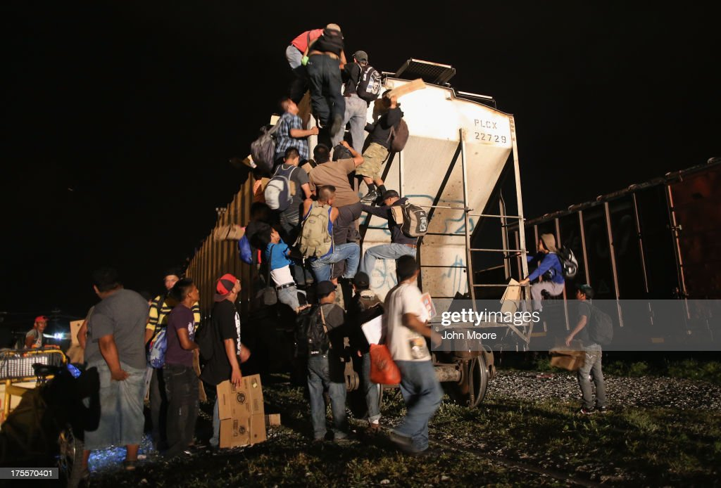 Central American migrants climb atop a freight train headed north early on August 4, 2013 in Arriaga, Mexico. Thousands of immigrants ride atop the trains, known as 'la bestia,' or the beast, during their long and perilous journey through Mexico to the U.S. border. Many of the immigrants are robbed or assaulted by gangs who control the train tops, while others fall asleep and tumble down, losing limbs or perishing under the wheels of the trains. Only a fraction of the immigrants who start the journey will arrive safely on their first attempt to illegally enter the United States.