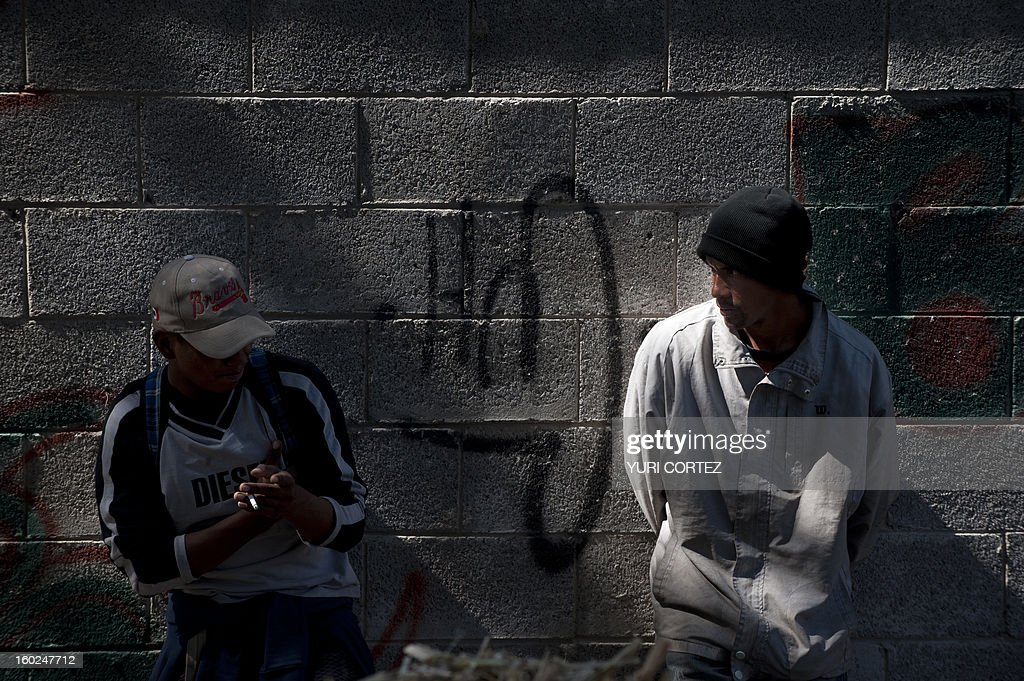 Central American migrants --mainly from La Ceiba, Honduras-- take a rest on a railway in Huehuetoca, Mexico state, on January 28, 2013. A group of university students, religious people and humanitarian movements inaugurated a dining room for migrants from differents countries travelling through Mexico on their way to the US border. AFP PHOTO/Yuri CORTEZ