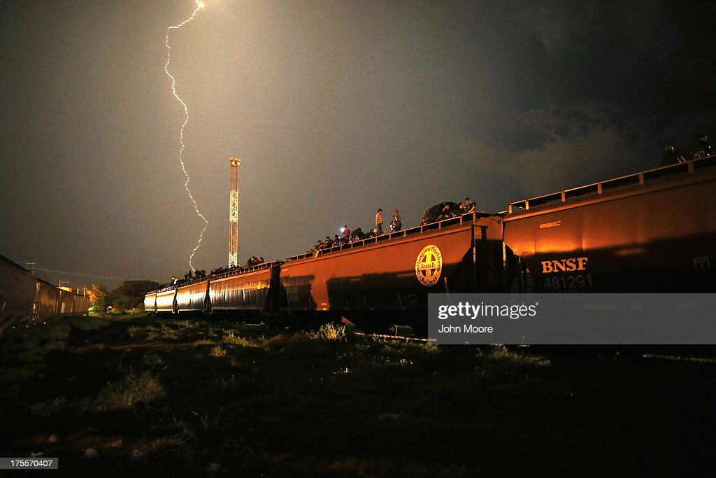 Central American migrants stand atop a freight train headed north early on August 4, 2013 in Arriaga, Mexico. Thousands of immigrants ride atop the trains, known as 'la bestia,' or the beast, during their long and perilous journey through Mexico to the U.S. border. Many of the immigrants are robbed or assaulted by gangs who control the train tops, while others fall asleep and tumble down, losing limbs or perishing under the wheels of the trains. Only a fraction of the immigrants who start the journey will arrive safely on their first attempt to illegally enter the United States.