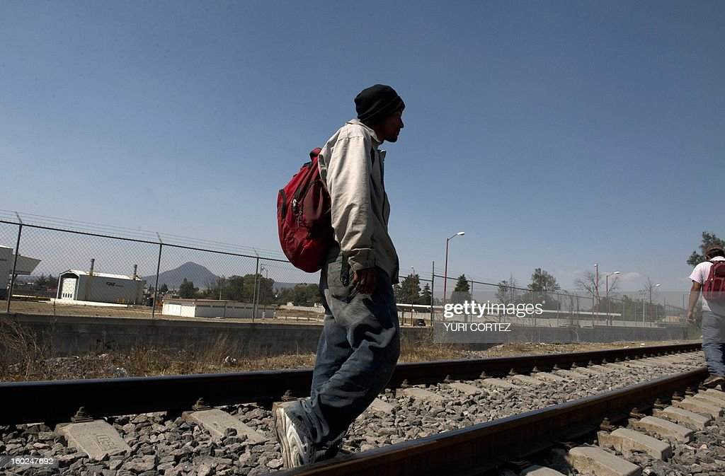 Central American migrants walk along a railway in Huehuetoca, Mexico state, on January 28, 2013. A group of university students, religious people and humanitarian movements inaugurated a dining room for migrants from differents countries travelling through Mexico on their way to the US border. AFP PHOTO/Yuri CORTEZ
