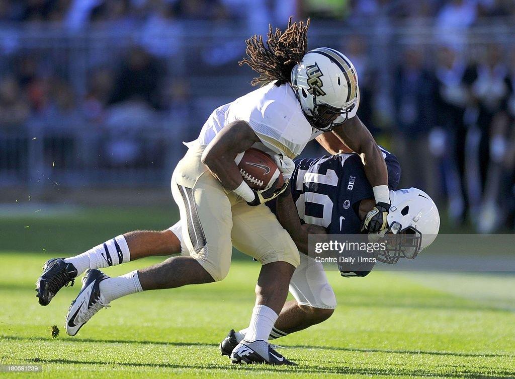 Central Florida's Rannell Hall bowls over Penn State's Trevor Williams on Saturday, September 14, 2013, at Beaver Stadium in University Park, Pennsylvania. UCF prevailed, 34-31.