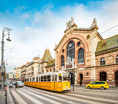 Central Market Hall in Budapest city, Hungary, Europe. Pedestrian crossing and yellow tram in foreground, old building and blue sky in background.