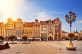 Central market square in Wroclaw Poland with old colourful houses, street lantern lamp and walking tourists people at gorgeous stunning morning sunrise sunshine. Travel vacation concept.