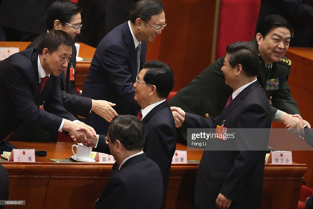 Central officials shake hands with former Chinese president Hu Jintao and newly-elected Chinese President Xi Jinping after the closing session of the National People's Congress (NPC) at the Great Hall of the People on March 17, 2013 in Beijing, China. China's newly-elected president Xi Jinping pledged Sunday to resolutely fight against corruption and other misconduct in all manifestations.