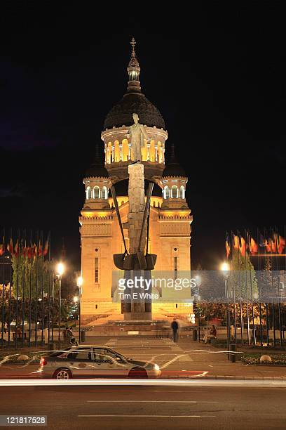 Central square with traffic at night with orthodox church and statue of Cluj Napoca, Romania