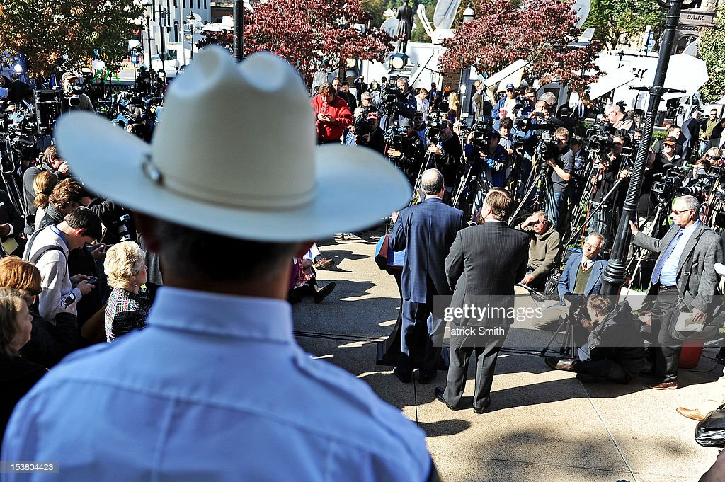 Centre County Sheriff Denny Nau watches over as Jerry Sandusky's defense attorney Joe Amendola answers questions to the media outside the Centre County Courthouse following former Penn State assistant football coach Jerry Sandusky being sentenced in his child sex abuse case on October 9, 2012 in Bellefonte, Pennsylvania. The 68-year-old Sandusky was sentenced to at least 30 years and not more that 60 years in prison for his conviction in June on 45 counts of child sexual abuse, including while he was the defensive coordinator for the Penn State college football team.