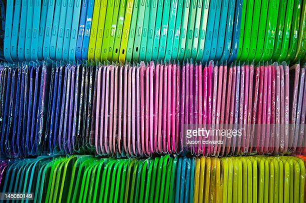 Rows of colourful mobile cases stacked in a shop window for sale.