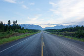 Shot from the centre of a long straight deserted stretch of Alaska Highway in Kluane National Park, Yukon Territory, Canada.