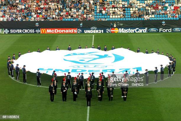Centrecircle ball boys and girls encircle the UEFA logo as the brass band wait to play the national anthems