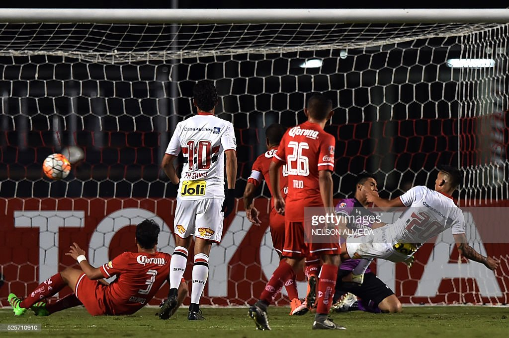 Centurion (R) of Brazils Sao Paulo kicks the ball to score against Mexico's Toluca during their 2016 Copa Libertadores football match held at Morumbi stadium, in Sao Paulo, Brazil, on April 28, 2016. / AFP / NELSON