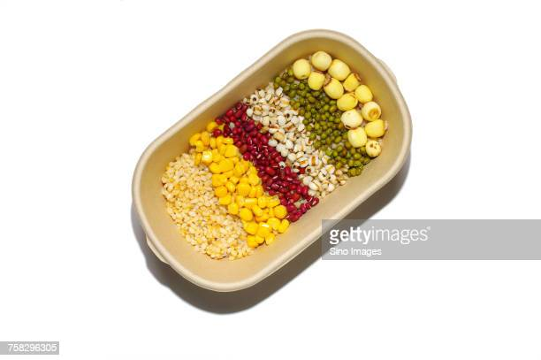 Ceramic bowl full of barley groats, sweet corn and red and green lentils