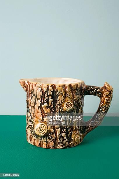 A ceramic creamer made to look like tree bark