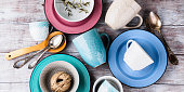 Ceramic crockery tableware on wooden background. Pastel vintage color bowls, dishes, cups