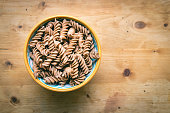 Ceramic dish filled with raw wholemeal fusilli pasta on a light wooden table and copy space