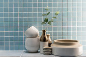 ceramic vase and bowl decoration in a bathroom with blue mosaic tile