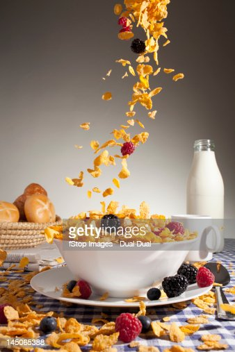 Cereal and fruit being poured into a bowl