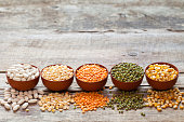 Bowls of cereal grains: red lentils, green mung, corn, beans and peas on wooden table.