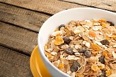Muesli with dried fruits in bowl. Isolated on wooden background