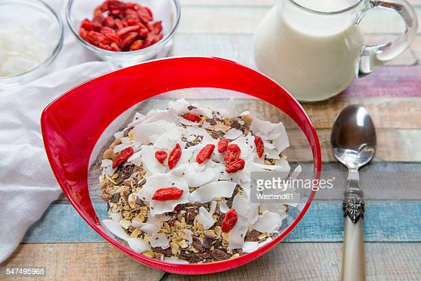Cereal with chia seeds, coconut chips, wolfberries and milk on wood