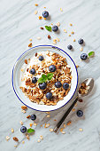 Cereals breakfast with blueberries on a marble background. Healthy morning meal with fresh berries. Top view