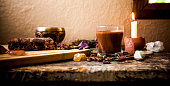 Ceremonial Cacao Beverage (Raw Chocolate), surrounded by ingredients, gemstones, a Tibetan singing bowl and candle.
