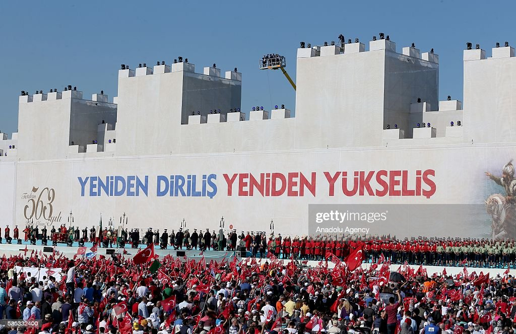 Ceremonial Ottoman Janissary Band stand in front of the giant model of a part of Istanbul's historical city walls with a slogan on it reading 'Again resurrection, again rising' during the celebrations of the 563rd anniversary of Istanbuls conquest by Turks at Yenikapi Event Area in Istanbul, Turkey on May 29, 2016. On May 29, 1453, Ottoman Sultan Mehmed II (Mehmet the Conqueror) conquered Istanbul, then called Constantinople, from where the Byzantines had ruled the Eastern Roman Empire for more than 1,000 years. The conquest transformed the city, once the heart of the Byzantine realm, into the capital of the new Ottoman Empire.
