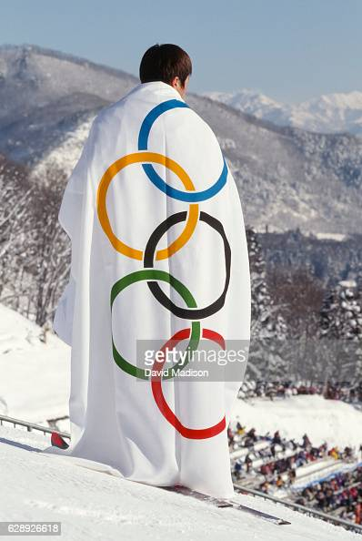 A ceremonial participant wraps himself in the Olympic flag during a ski jumping event of the XVIII Winter Olympic Games held during February 1998 in...