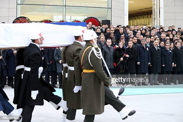 Ceremonial soldiers carry the coffin of Russian ambassador to Turkey Andrei Karlov as his wife Marina Karlov mourns during the farewell ceremony that...