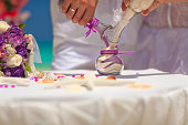 The bride and groom pour colorful sand in the container. Ceremony colored sand.
