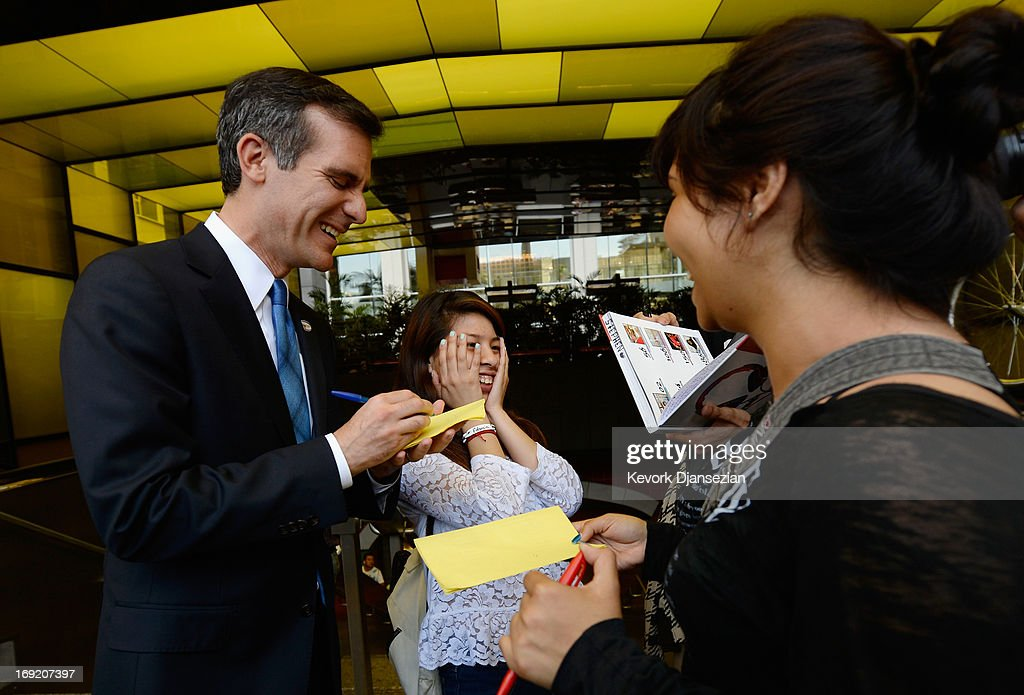 CErika Espinoxa (C) student at Hollywood High School poses as candidate in the Los Angeles City mayoral race, Councilman Eric Garcetti gives his autograph to a group of students on Hollywood Boulevard as he campaigns in the closing hours run-off election on May 21, 2013 in the Silver Lake area of Los Angeles, California. In what could be a record-low voter turnout, Garcetti is up against Los Angeles City Controller Wendy Greuel for the seat held by two-term Antonio Villaraigosa.