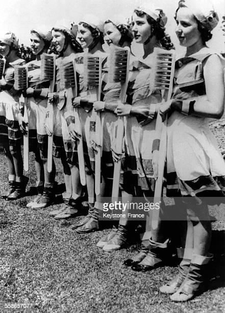 Ces gentilles ecolieres armees d'enormes brosses a dents font des exercices de culture physique au cours d'une 'fete de l'hygiene' organisee par un...