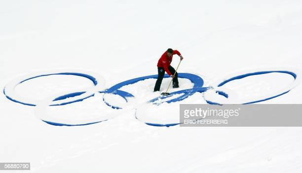 A man brushes snow off the Olympic rings prior to the start of the men's 125km biathlon pursuit race at the Turin 2006 Winter Olympics 18 February...