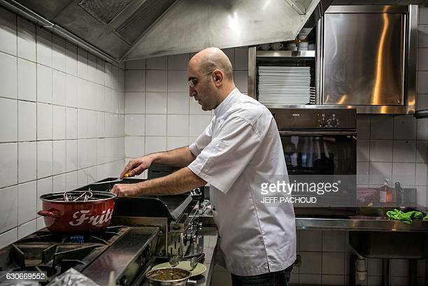 Cesar Asfar refugee from Syria and restaurant owner works in the kitchen of his restaurant 'Delices D'Alep' in Tournus eastern France on December 29...