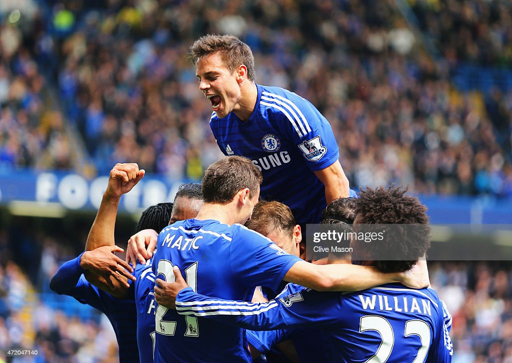 Cesar Azpilicueta of Chelsea (top) and team mates mob Eden Hazard (obscured) as he scores their first goal during the Barclays Premier League match between Chelsea and Crystal Palace at Stamford Bridge on May 3, 2015 in London, England.
