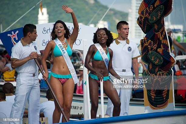 Cesar department's contestant Andrea Salas and Choco's department Yesuly Londono wave during the 'Desfile en Balleneras' in Cartagena Colombia on...