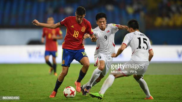 Cesar Gelabert of Spain is challenged by Kim Chung Jin and Cha Kwang of Korea DPR during the FIFA U17 World Cup India 2017 group D match between...
