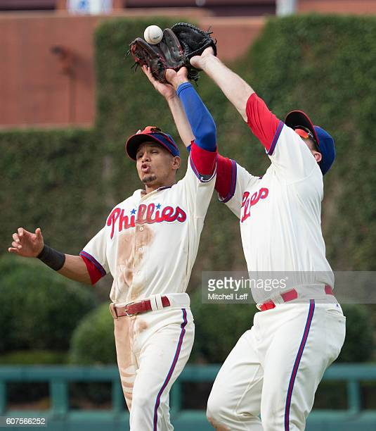 Cesar Hernandez and Tommy Joseph of the Philadelphia Phillies cannot make the catch on a pop up hit by Marcell Ozuna of the Miami Marlins in the top...
