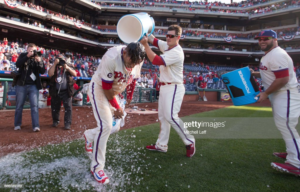 Cesar Hernandez #16 of the Philadelphia Phillies gets ice and Powerade poured on him by Tommy Joseph #19 and Cameron Rupp #29 of the Philadelphia Phillies after hitting a walk off single in the bottom of the ninth inning against the Washington Nationals at Citizens Bank Park on April 9, 2017 in Philadelphia, Pennsylvania. The Phillies defeated the Nationals 4-3.