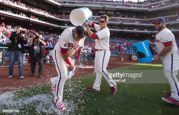 Cesar Hernandez of the Philadelphia Phillies gets ice and Powerade poured on him by Tommy Joseph and Cameron Rupp of the Philadelphia Phillies after...
